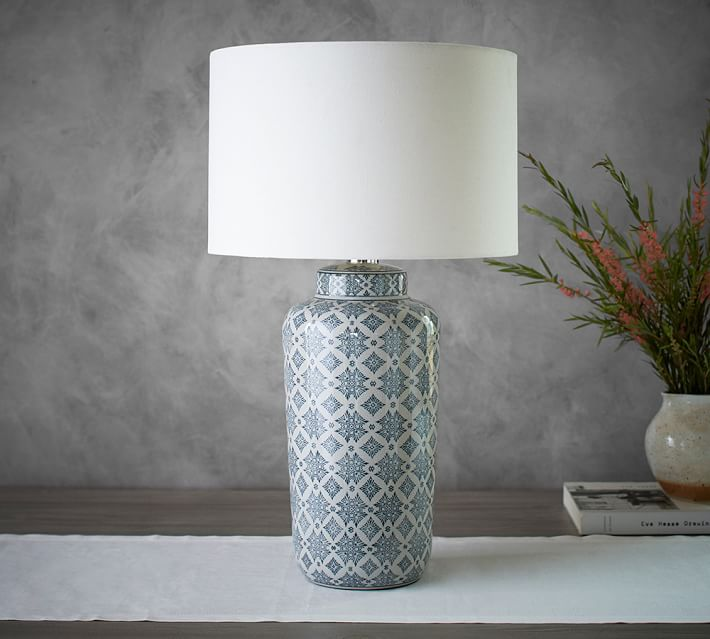 A blue and white patterned lamp on a white table runner.