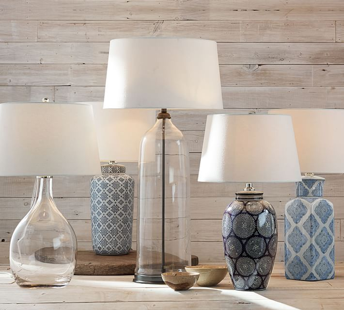 Blue and white plus clear glass lamps on a wooden table displayed.