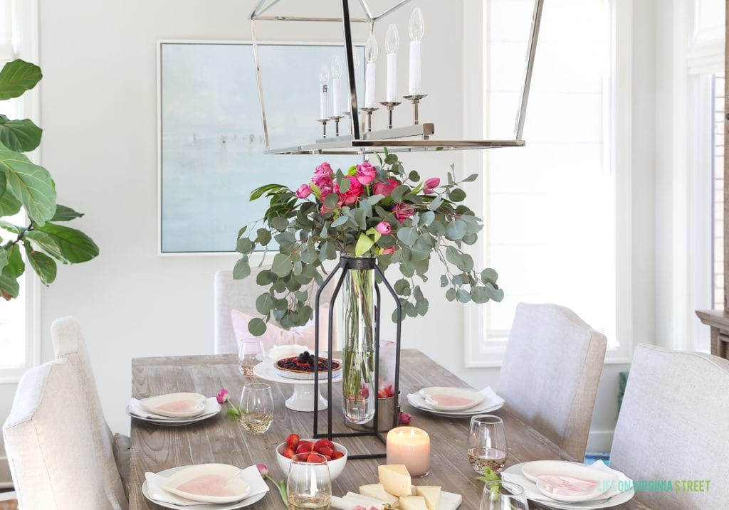 A tall floral and eucalyptus vase, linen chairs, reclaimed wood table, beach art, and heart plates on the dining room table.