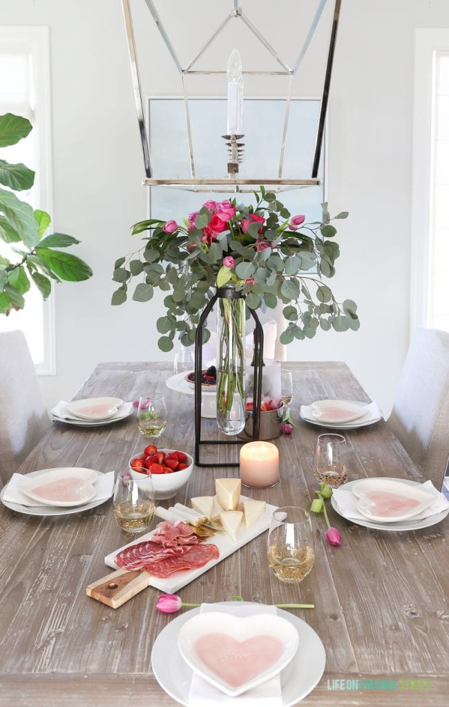 Valentine's Day entertaining and tablescape with tall floral and eucalyptus vase, linen chairs, reclaimed wood table, beach art, and heart plates. A fresh and colorful tablescape!