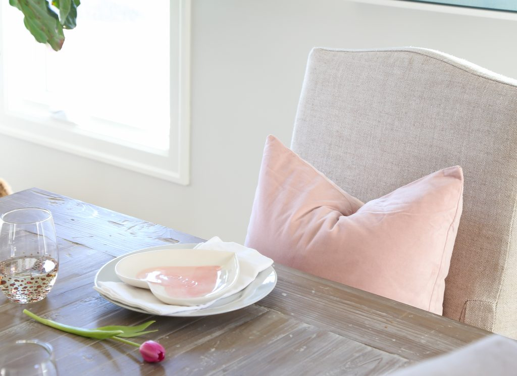 A heart shaped plate with a pink tulip beside it and a pink pillow on the chair.
