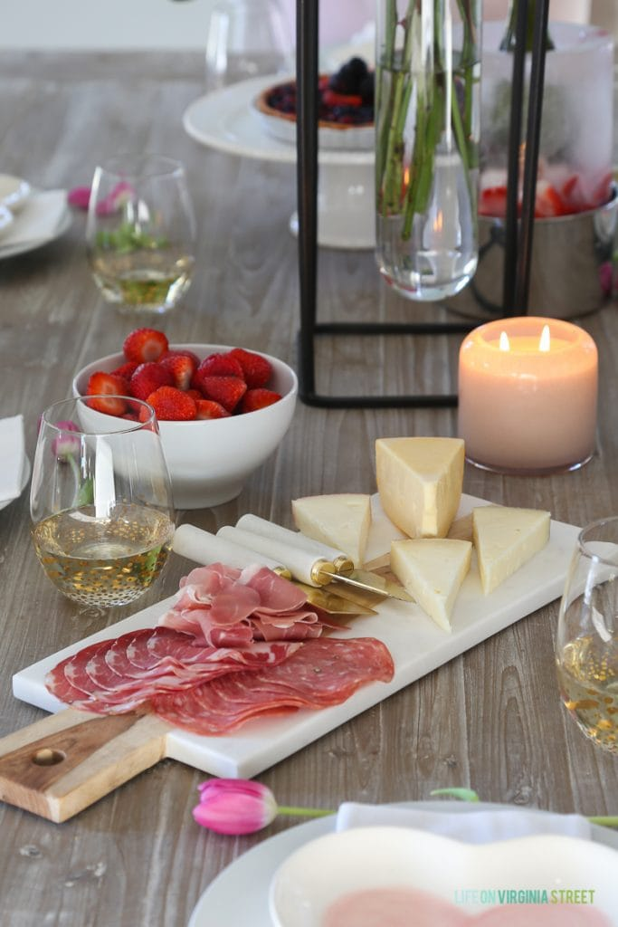 A meat and cheese tray with strawberries in a bowl and candles on the table.