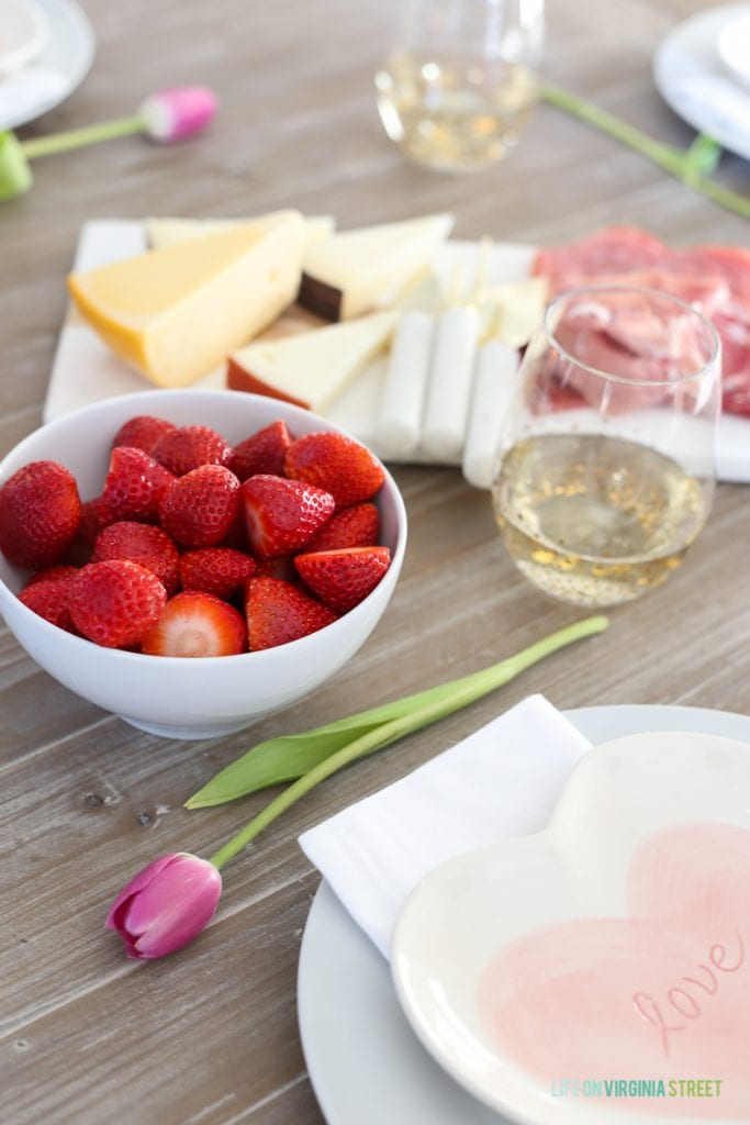 A bowl of strawberries, cheese and white wine on the table.