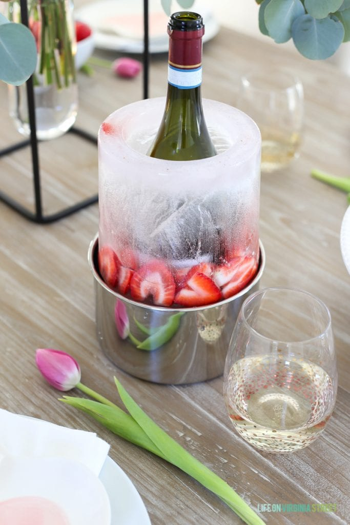 A bottle chiller with wine on the table and a tulip beside it.