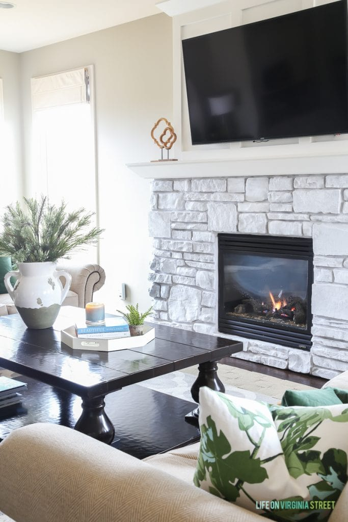 Great tips for winter home maintenance. Neutral winter decor with green fig leaf pillow, dark green velvet and pine boughs. #ad