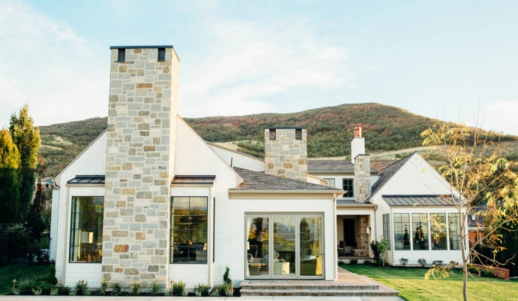 A white brick Utah home with black window trim and neutral stone accents.