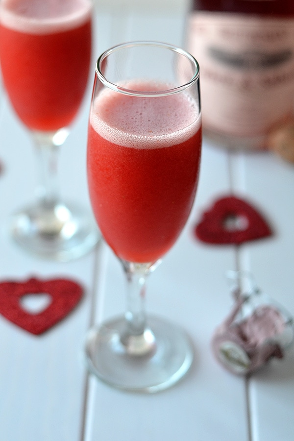 Strawberry bellini in a champagne glass on the table.