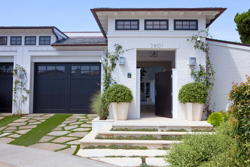 white exterior with black window frames and black garage via molly wood garden designs