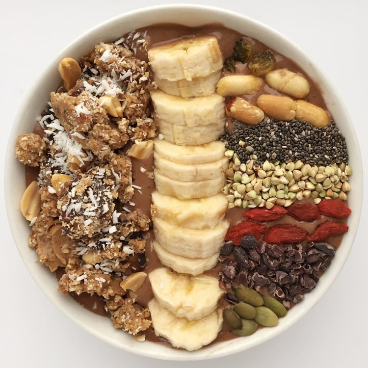 Chocolate Maca Peanut Butter Smoothie Bowl with fresh cut bananas and nuts on top.