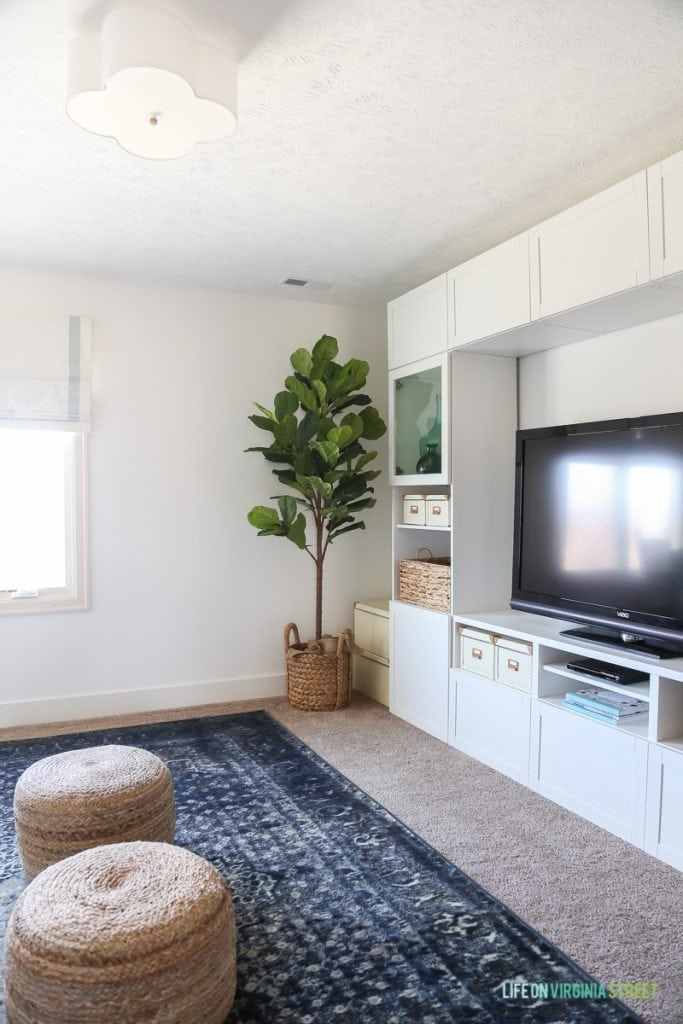 TV and craft room with Benjamin Moore Simply White walls, fiddle leaf fig tree, scalloped light fixture, blue vintage-style rug and sisal poufs.