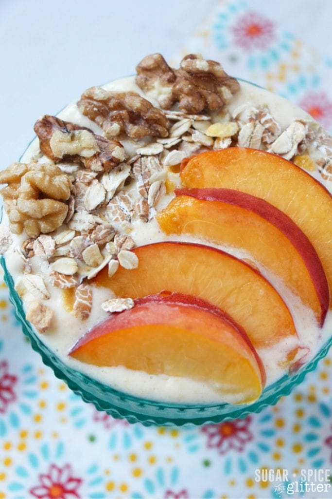 Peach pie smoothie bowl with peach slices and walnuts on top.