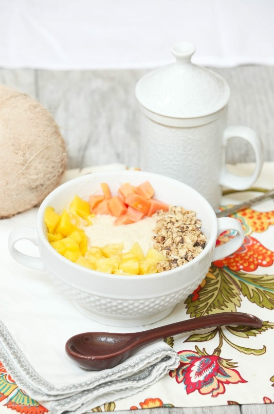 Pina colada protein smoothie bowl in a white bowl with a spoon beside it.