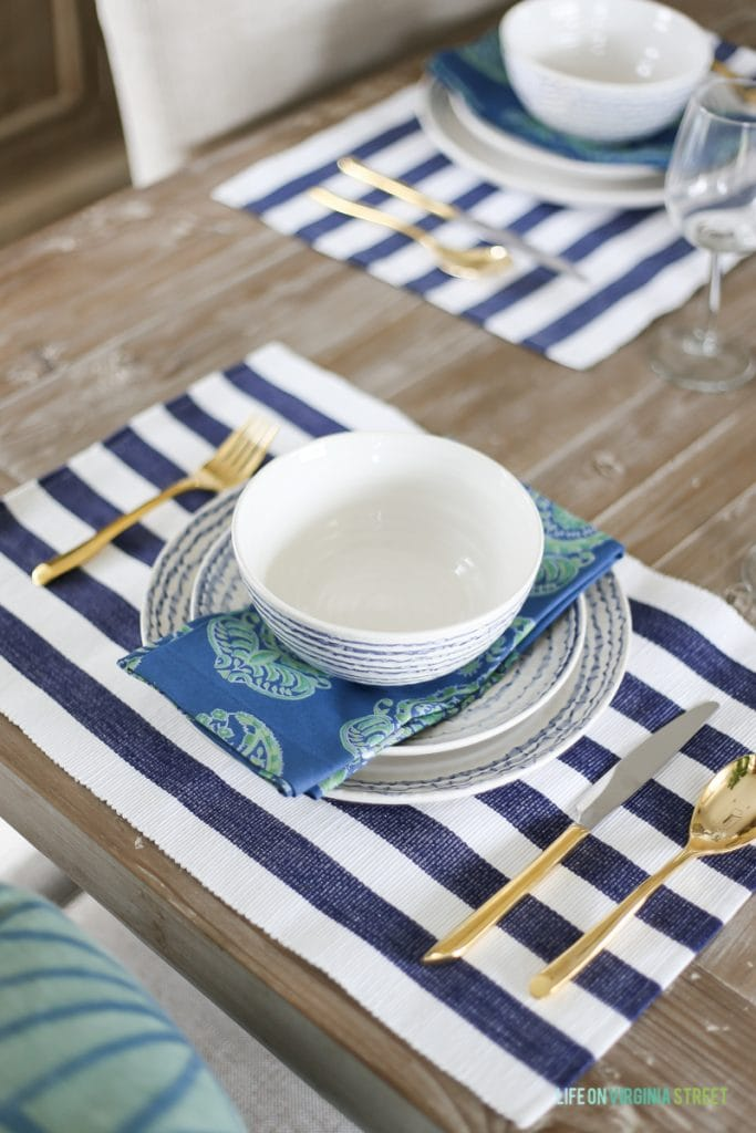 A coastal inspired tablescape with navy blue and white striped placemats, blue paisley napkins, blue squiggle dishes, white hydrangeas, beach art, linen dining chairs, reclaimed wood hutch, driftwood table, fiddle leaf fig tree, gold silverware and blue striped rug.