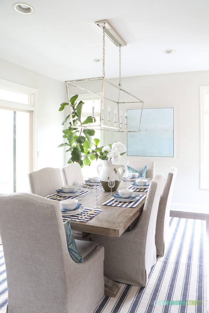 A coastal inspired tablescape with navy blue and white striped placemats, blue paisley napkins, blue squiggle dishes, white hydrangeas, beach art, linen dining chairs, reclaimed wood hutch, driftwood table, Darlana, linear pendant, fiddle leaf fig tree, gold silverware and blue striped rug.