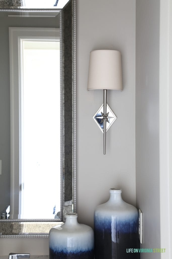 Neutral powder bathroom with Behr Castle Path walls, Benjamin Moore Hale Navy vanity cabinets, indigo ombre vases, and chrome star sconces.
