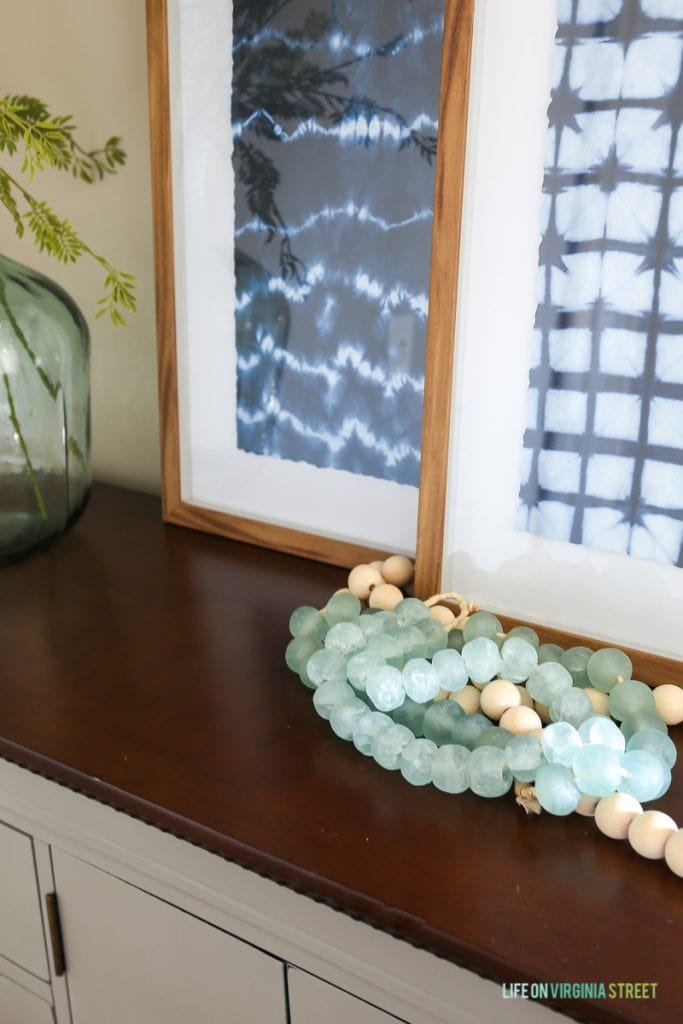 Gray buffet table dresser with indigo shibori artwork, glass demijohn, wood and glass beads, faux greenery, and woven basket. Walls are Behr Castle Path.