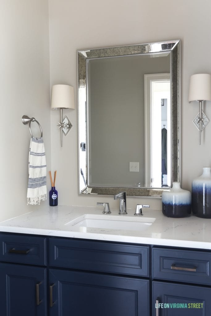 Neutral powder bathroom with Benjamin Moore Hale Navy navy blue cabinets, chrome star sconces, blue ombre vases, and Daltile One Quartz in the Luminesce.