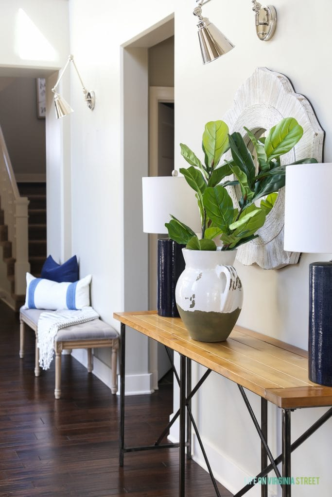 Gorgeous neutral entryway hallway with gray linen driftwood bench, gray and white striped throw, wood and iron console table, navy blue linen lamps, chrome swing-arm sconces, and faux fiddle leaf fig stems.