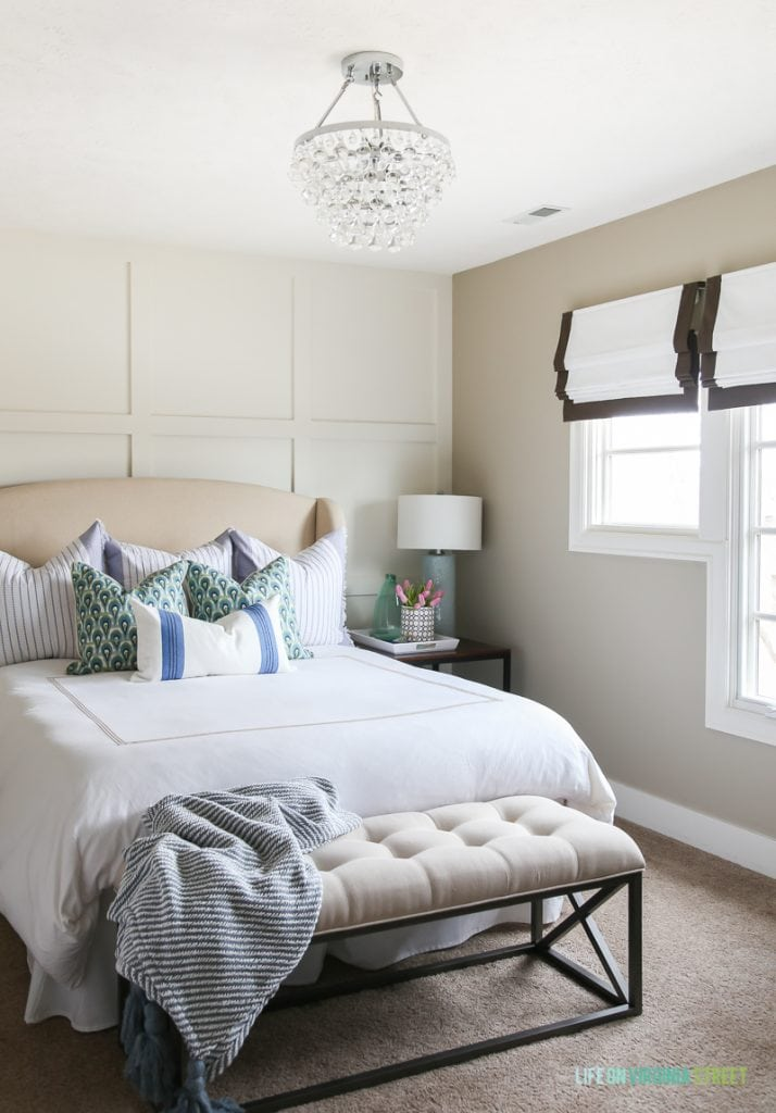 Spring guest bedroom with white bedding, ribbon trimmed roman shades, glass chandelier, pink tulips, board and batten feature wall, and blue and green accents.