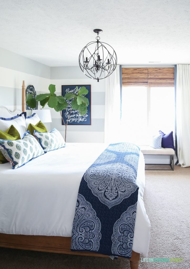 Guest bedroom with woven shades, ribbon trimmed drapes, white bedding, navy blue paisley throw, Doxology canvas, fiddle leaf fig tree, chartreuse velvet pillows and hickory wood bed.
