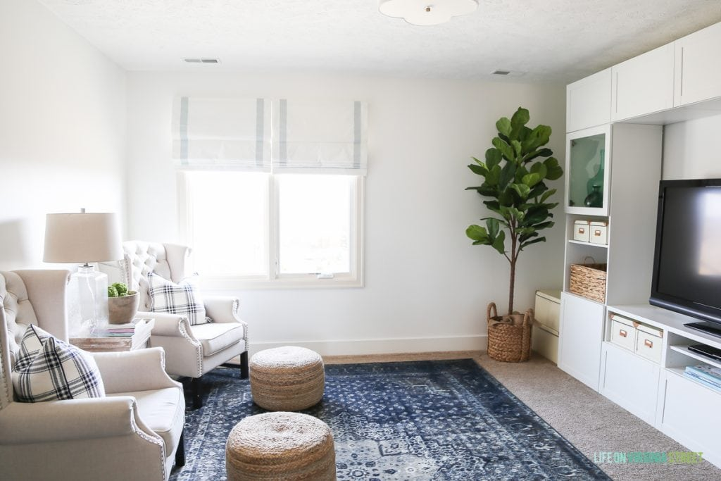 Linen chairs, blue vintage rug, ribbon trimmed roman shades, sisal poufs and Behr Simply White Walls. Love the scalloped light fixture and IKEA BESTA entertainment center!