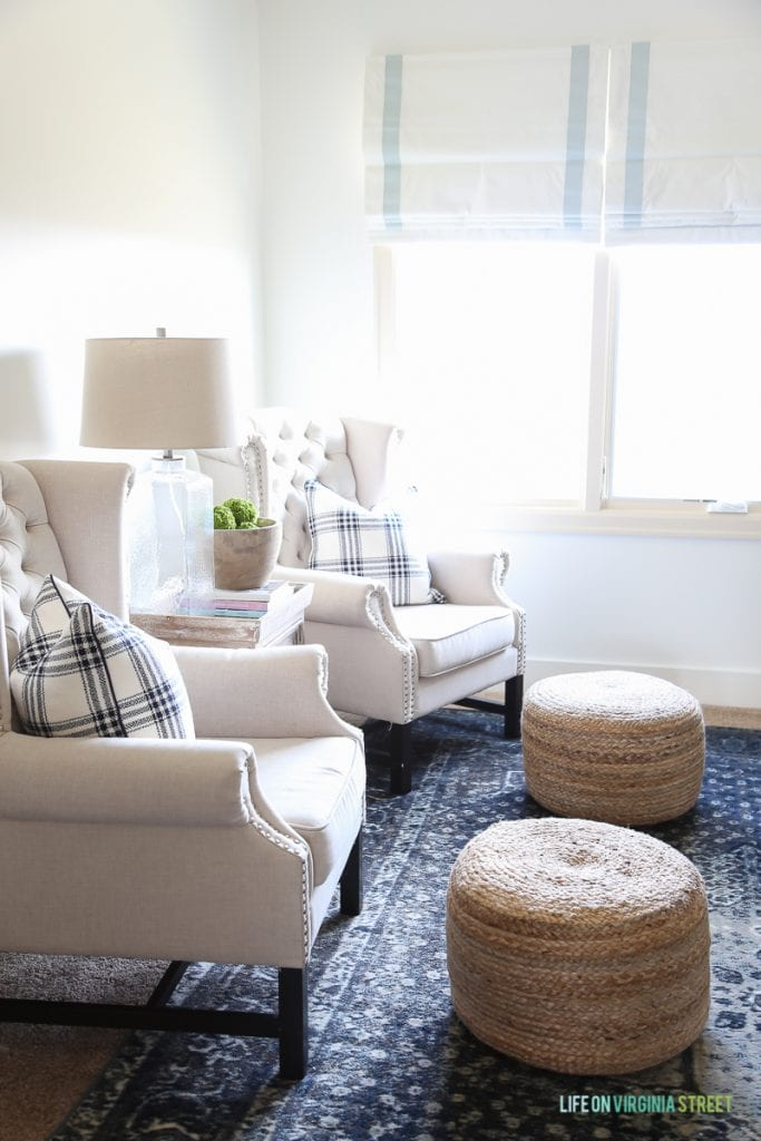 Linen chairs, blue vintage rug, ribbon trimmed roman shades, sisal poufs and Behr Simply White Walls.