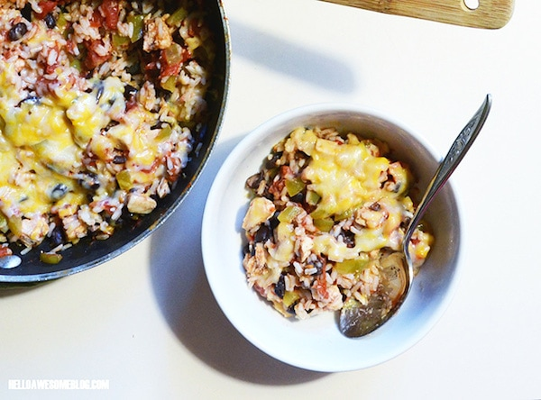 A skillet with cheesy chicken burrito and also a bowl filled with the burrito and a spoon.