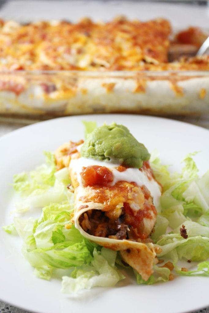 A cheesy baked burrito with a dollup of guacamole on top and shredded lettuce underneath it.