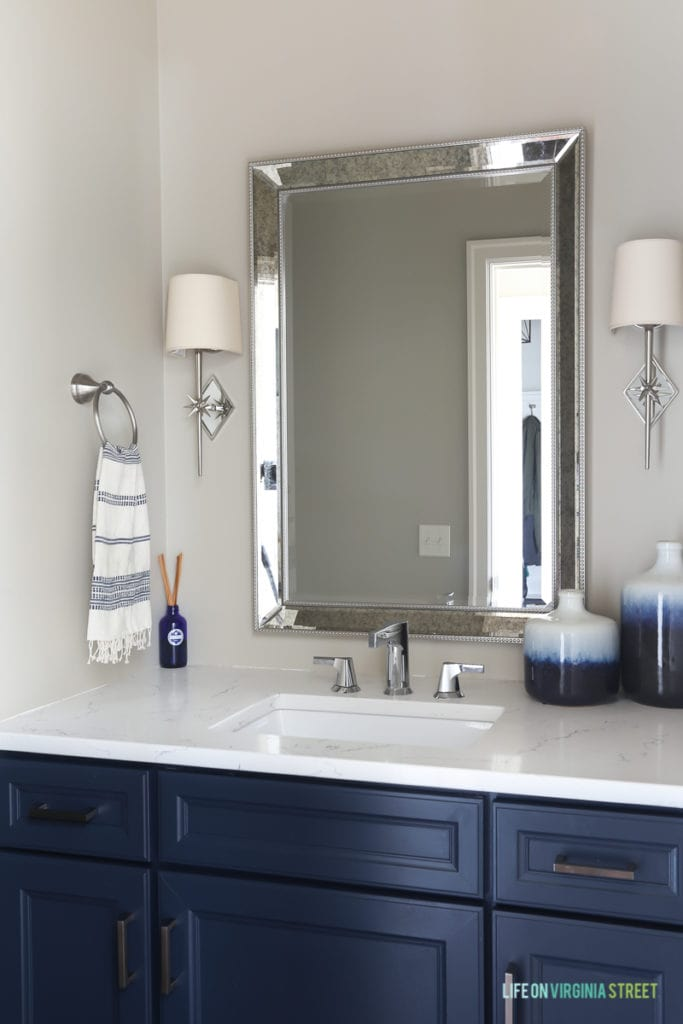 Thermofoil cabinets painted with Benjamin Moore Hale Navy. Loving the chrome star sconces, the beaded mirror, and white marble-like countertops!