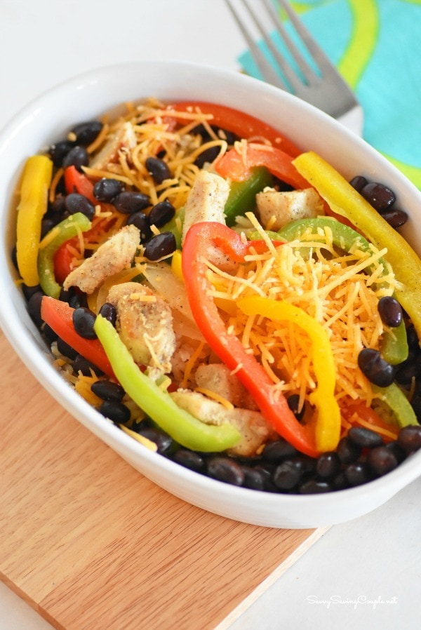 A bowl full of black beans, cheese, green, yellow and red peppers.