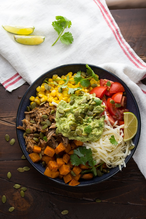 A maple pulled pork burrito bowl with corn, and guacamole.