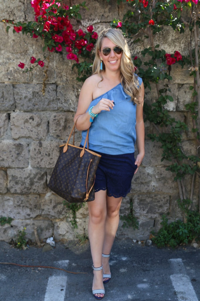 A woman (Sarah) in shorts, a blue shirt and sunglasses in front of a floral vine growing on a stone wall.