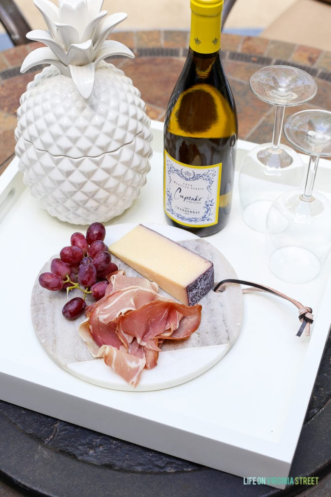 Marble cheese board with prosciutto, grapes, and cheese on a white serving tray. Love the white ceramic pineapple and the oleander tree in the background.