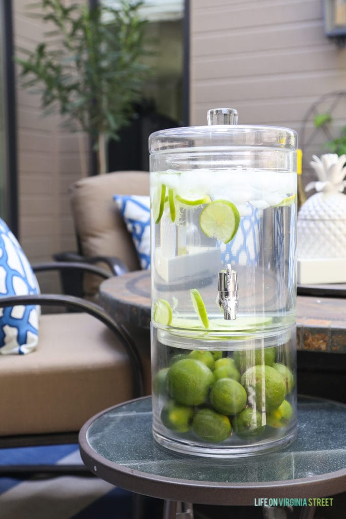 Two-tiered beverage dispenser. Love the limes in combination with this beautiful blue and white outdoor entertaining area.