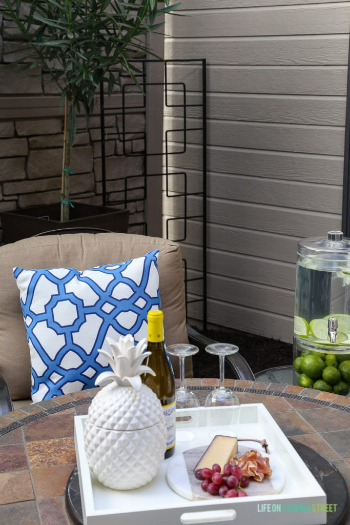 Gorgeous before and after tour of this outdoor courtyard entertaining space. Love the blue and white striped rug, the blue and white trellis pillows, the oleander topiaries, the limes in the beverage dispenser, the white ceramic pineapple, and more!
