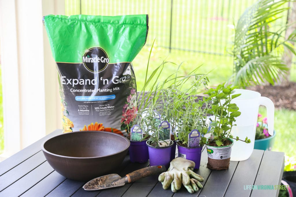 Pots of plants, soil in a bag, gardening gloves and gardening tools on the outdoor table.
