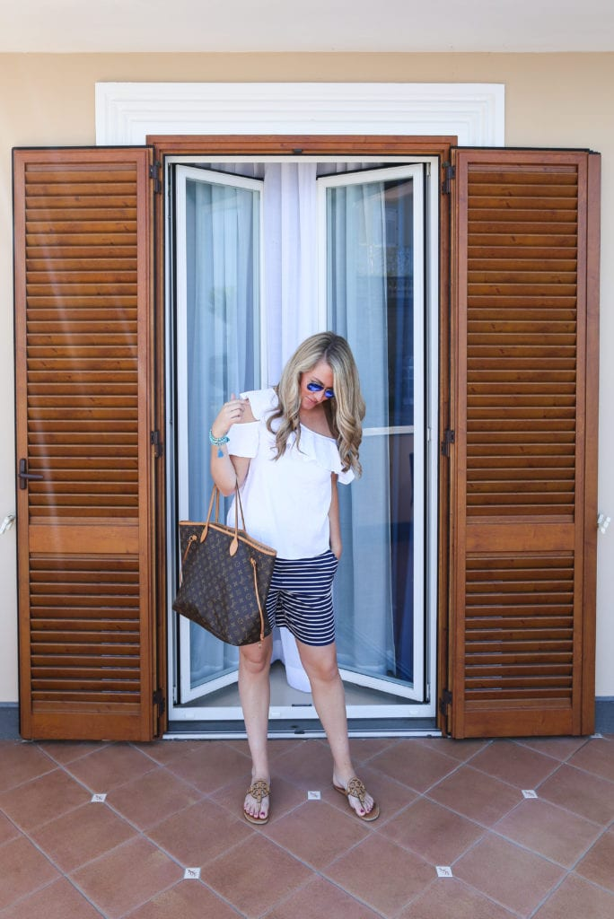 Sarah in shorts, a white top and a large purse.