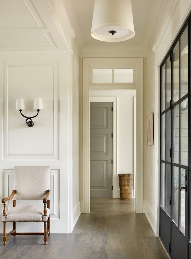 Tan interior front door with darker French doors beside it. A light gray floor color and white chair in the hallway.