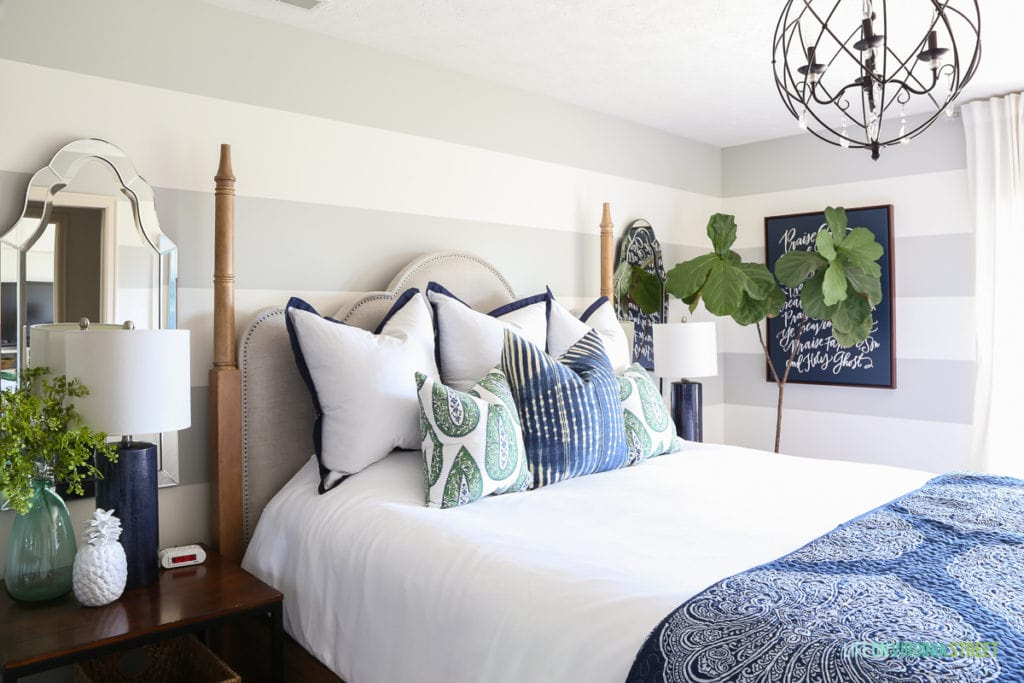 Side view featuring bedroom with gray and white striped walls, white bedding, blue and green paisley pillows, navy blue linen lamps, iron orb chandelier and a navy blue Lindsay Letters Doxology canvas.