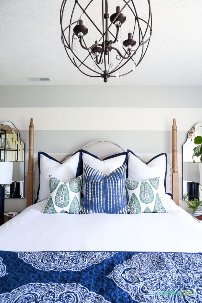 Above the bed featuring, paisley pillows and iron orb chandelier.