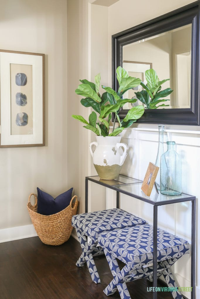 A beachy entryway vignette with blue and white patterned x-leg benches, seagrass basket, fiddle leaf fig stems, recycled glass vases, framed agate artwork, a wood frame, black mirror and navy blue velvet pillow.