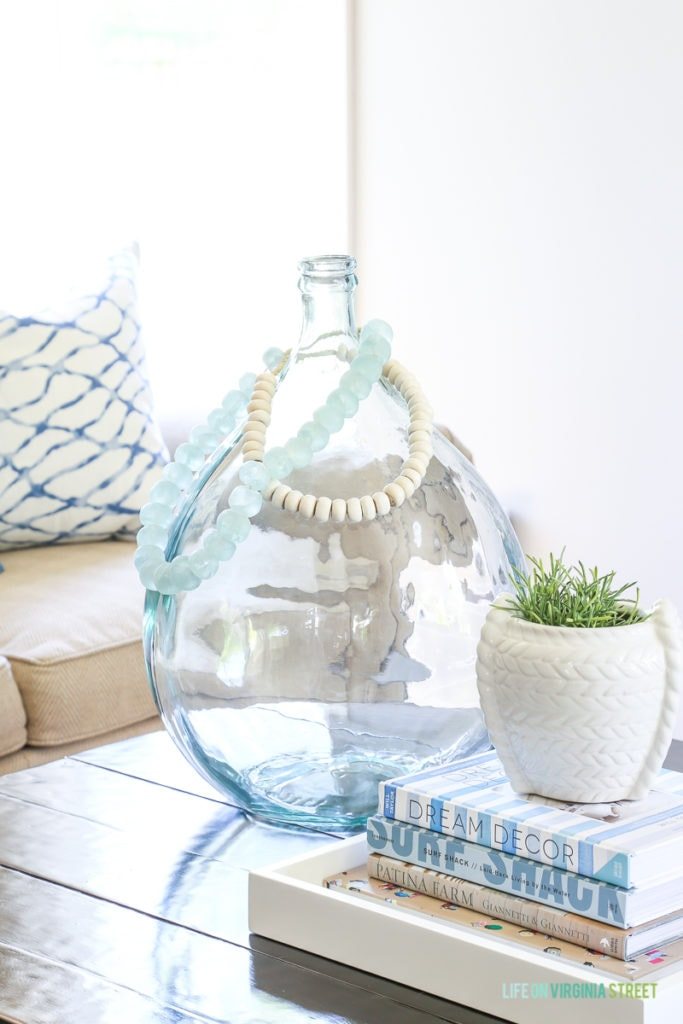 Sea glass beads on a large demijohn vase. Love this coastal style vignette that's perfect for a blue and white living room!