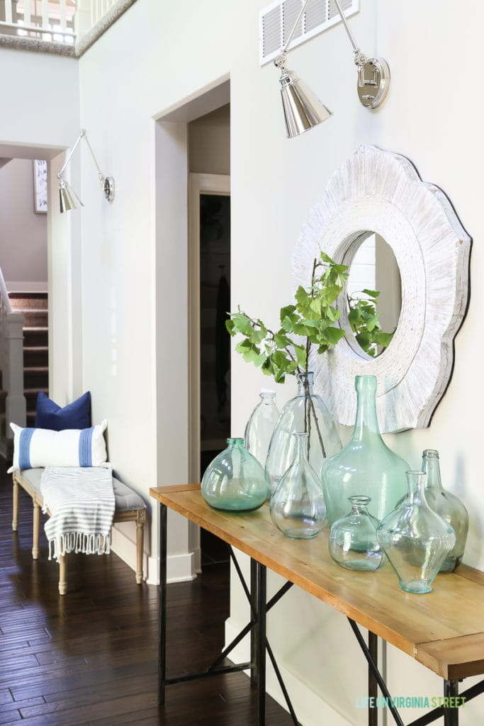 A coastal style entryway with linen bench, striped throw, blue and green recycled glass vases, polished nickel swing-arm sconces and gingko stems make the perfect beachy vibe!