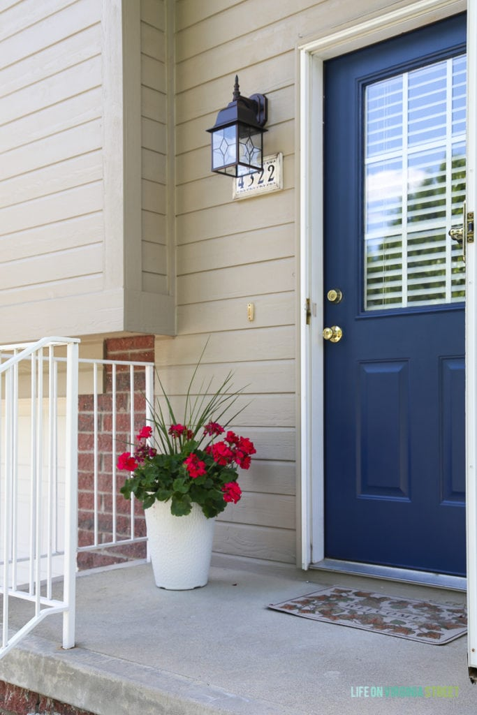 Adding curb appeal with a freshly painted navy blue door, new lighting, and hot pink geranium flowers. Paint color is TrueValue's Easy Care Ultra Premium in Ink Pad. Love the gorgeous, saturated blue color.