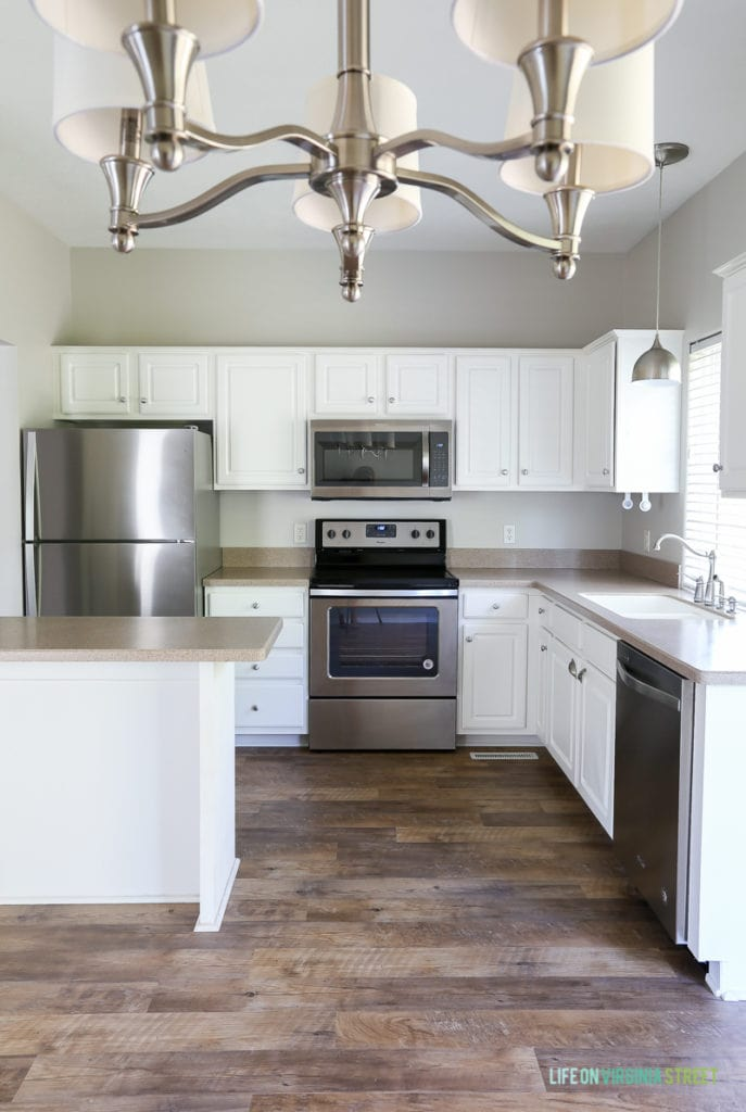 Rental house kitchen and dining makeover. Flooring is Adura Max® Plank Dockside Sand and wall color is Sherwin Williams Agreeable Gray.