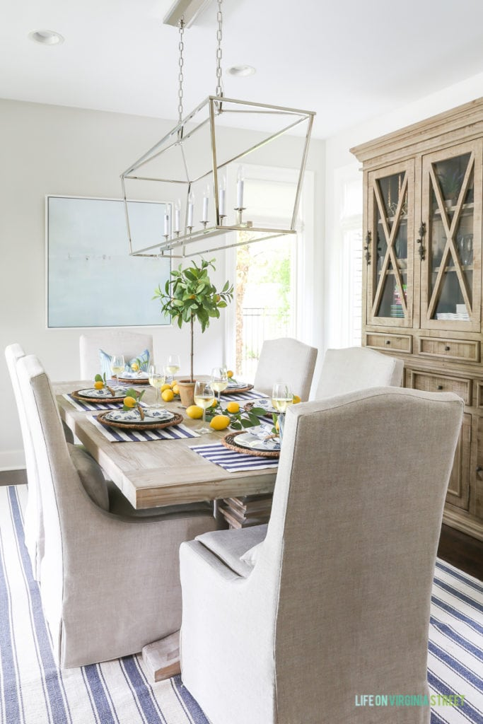 A beautiful summer tablescape inspired by the Amalfi Coast in Italy. Lemons, navy blue and white stripes, linen chairs, Darlana linear pendant, wood hutch, beach art, reclaimed wood table and wine!