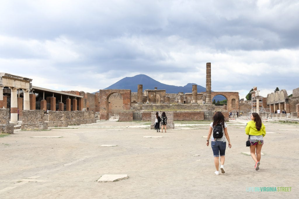 A main square in Pompeii with a couple of tourists there.