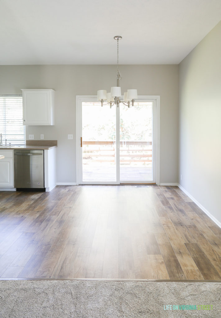 Rental house kitchen and dining makeover. Flooring is Mannington Adura Max® Plank Dockside Sand and wall color is Sherwin Williams Agreeable Gray.