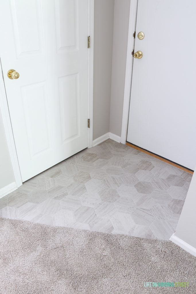 Garage door entrance makeover using Mannington Luxury Vinyl in Hive Pollen. Love that this looks like marble hex tiles!