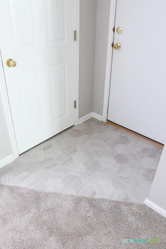 Garage door entrance makeover using Mannington Luxury Vinyl in Hive Pollen. Love that this looks like marble hex tiles!